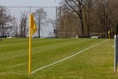 Amateur soccer field. With green lawn and white lines with yellow pole on the corner edge royalty free stock photo