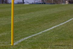 Amateur soccer field. With green lawn and white lines with yellow pole on the corner edge royalty free stock photos