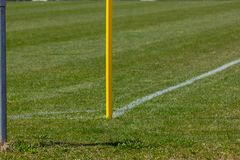 Amateur soccer field. With green lawn and white lines with yellow pole on the corner edge stock images