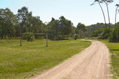 Amateur soccer field with wooden goals near a road. Road with soccer field and trees Royalty Free Stock Photo