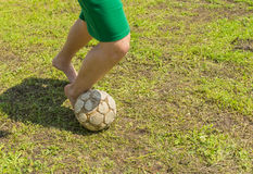 Amateur soccer on old and bad field. With shabby ball and barefoot royalty free stock images