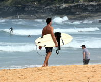 Amateur surfer is walking on the beach with his surfboard. Sydney, Australia - March 13, 2016. Amateur surfer is walking on the beach with his surfboard royalty free stock photography