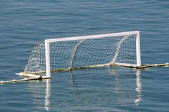 Amateur water polo goal with white frame and dense net supported with rope and floating buoys resting on calm sea. On warm sunny day stock image