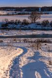 Amateur winter landscape with riversice and footpath in snow.  royalty free stock photography