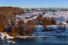 Amateur winter riverside landscape with birch forest and slope.  royalty free stock photos