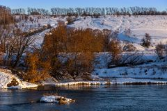 Amateur winter riverside landscape with birch forest and slope.  stock image
