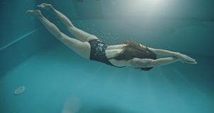 Amateur woman swimmer, dolphin style. Amateur woman swimmer inside swimming pool stock footage