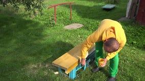 Amateurarbeitskraftjungen-Malereiholzoberfläche mit Bürste in der gelben Farbe nahaufnahme 4K stock video footage