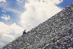 Amateurbergsteigen gegen den blauen Himmel mit Wolken Bemannen Sie Hügel oben klettern, um die Spitze des Berges zu erreichen Aus stockfotos