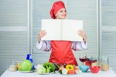 Amateurkok gelezen boekrecepten Het meisje leert recept Boek door beroemde chef-kok Verbeter het koken vaardigheid Boekrecepten a stock afbeelding