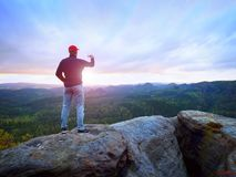 Amator bierze fotografie z telefonem na szczycie skała Marzycielski krajobraz, słońca zrozumienie na horyzoncie zdjęcie royalty free