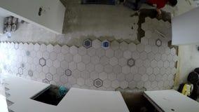 Amatorski mężczyzna kłaść sześciokąta kształta płytki na korytarz podłodze Statyczny timelapse zdjęcie wideo