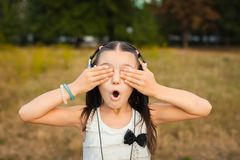 Amaze girl closing her eyes on nature. Joyful girl closing her eyes with hands on nature, funny girl with black and silver headphone listening song outdoor royalty free stock photos