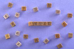 Amaze word metal block. Amaze word gold and silver metal block on blue paper with letter blocks around stock photo