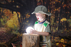 Amazed!. An adorable little explorer amazed by the light sphere she's found in a darkening autumn woods Royalty Free Stock Images