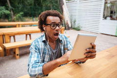 Amazed african young man with tablet sittign and shouting outdoors Royalty Free Stock Photography
