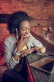 Amazed Afro-American woman covering mouth in shock at bar stock image