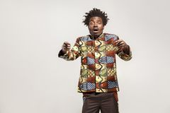 Amazed afro man pointing fingers at camera and shock. Indoor, isolated on gray background Stock Photos