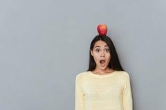 Amazed asombró a la mujer con la manzana en la situación y el grito de la cabeza Imagenes de archivo