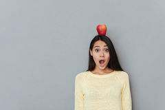 Amazed astonished woman with apple on head standing and shouting Stock Images