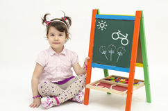 Amazed baby girl draw flowers and bike on black board with chalk. Amazed baby girl draw flowers, a bike and Sun on black board with chalk isolated on white Royalty Free Stock Image