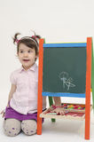 Amazed baby girl draw flowers on black board with chalk. Isolated on white background Royalty Free Stock Photo