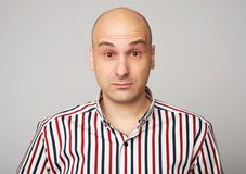 Amazed bald man. Middle aged guy wearing shirt isolated over grey studio wall Royalty Free Stock Photography