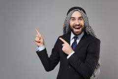 Amazed bearded arabian muslim businessman in keffiyeh kafiya ring igal agal classic black suit isolated on gray