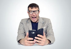 Amazed bearded man in glasses and jacket looking on smartphone opening his mouth Stock Image