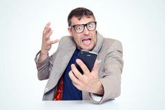 Amazed bearded man in glasses and jacket looking on smartphone opening his mouth Royalty Free Stock Photography