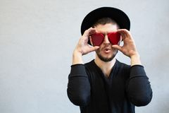Amazed bearded man holding red hearts on eyes. Dressed with in black, Valentines Day background. royalty free stock photos