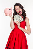 Amazed beautiful curly woman holding pink piggy bank and money Stock Images