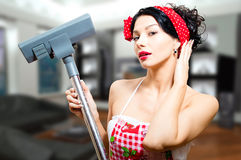 Amazed beautiful pinup lady holding hoover in Royalty Free Stock Images