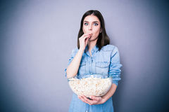 Amazed beautiful woman eating popcorn Royalty Free Stock Images