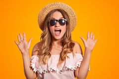 Amazed beautiful young European female in summer hat, trendy sunglasses and fashionable blouse, clasps hands, opens mouth, has ove royalty free stock images