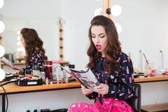 Amazed beautiful young woman sitting and reading fashion magazine Stock Images