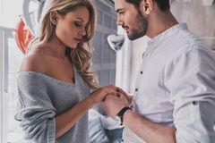 Amazed by the beauty of the ring. Beautiful young couple holding. Hands while standing at home Stock Image
