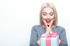 Amazed blond-haired woman getting present. Pleasant gesture. Portrait of young beautiful blond-haired woman getting big present on white isolated background Royalty Free Stock Photography