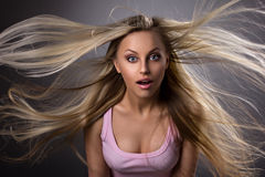 Amazed blond young woman. Portrait of a amazed blond young woman with waving hair and opened mouth on grey-dark background Royalty Free Stock Image