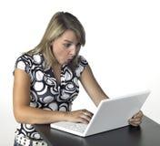 Amazed blonde computing girl Stock Photo