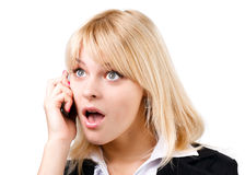 Amazed blonde girl talking on phone Royalty Free Stock Images