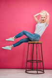 Amazed blonde woman sitting on the chair Stock Photography