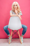 Amazed blonde woman sitting on the chair Royalty Free Stock Photo