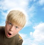 Amazed boy. Cute blond boy with surprised expression, on background of sky Stock Image