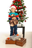 Amazed boy with Christmas gifts. Amazed boy standing in front of Christmas tree with presents and holding teddy bear Stock Photo
