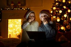 Amazed children using tablet near Christmas tree. Amazed boy and girl in Christmas hats sitting near brightly decorated Christmas tree and using tablet Royalty Free Stock Image