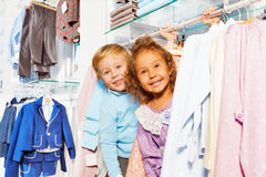Amazed boy and girl play hide-and-seek in shop Stock Photo