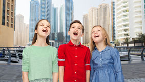 Amazed boy and girls looking up. Childhood, emotions, travel, tourism and people concept - happy amazed boy and girls looking up with open mouths over dubai city Stock Photo
