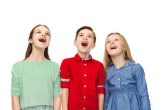 Amazed boy and girls looking up. Childhood, fashion, friendship and people concept - happy amazed boy and girls looking up with open mouths Royalty Free Stock Photos