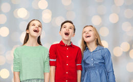 Amazed boy and girls looking up. Childhood, fashion, friendship and people concept - happy amazed boy and girls looking up with open mouths over holidays lights Royalty Free Stock Photography
